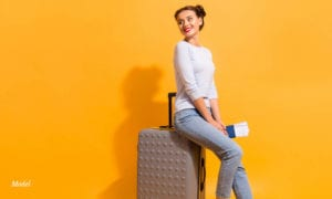 Young woman sitting on a Luggage on yellow background